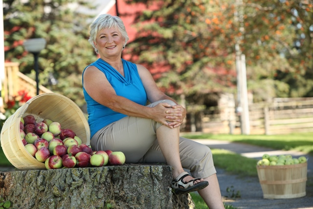 Cathy McKay sitting on a tree stump surrounded by apple baskets